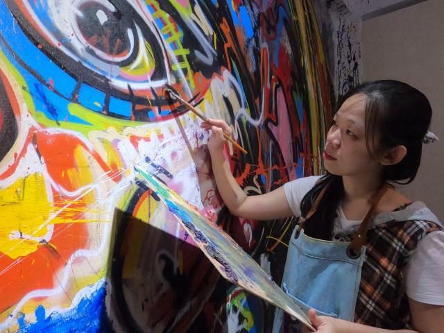 ภาพของผู้หญิงผมยาว ในเสื้อแขนสั้นกำลังวาดภาพกราฟิติบนกำแพง