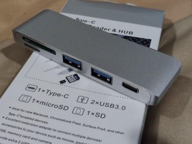 USB-C Hub สีเงิน อลูมิเนียม มีพอร์ต USB 3.1 Gen 1 สองพอร์ต พอร์ต USB-C (เป็น Power Delivery) 1 พอร์ต และสล็อตอ่าน SD card กับ MicroSD card อย่างละอัน