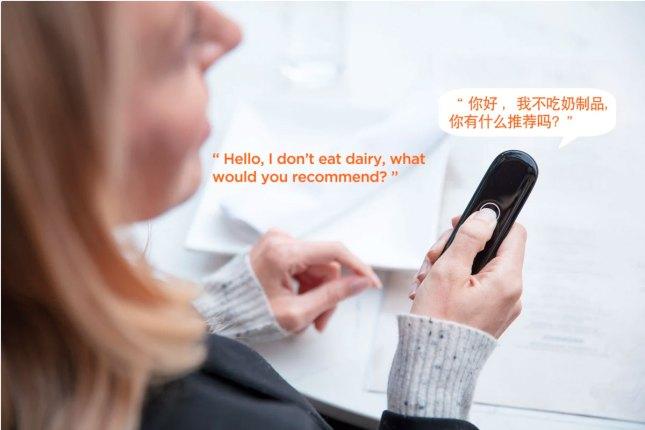 หญิงสาวชาวต่างชาติ ผมทอง ใส่เสื้อแขนยาว กำลังใช้งานเครื่องแปลภาษา Cheetah Talk แปลจากภาษาอังกฤษเป็นภาษาจีน