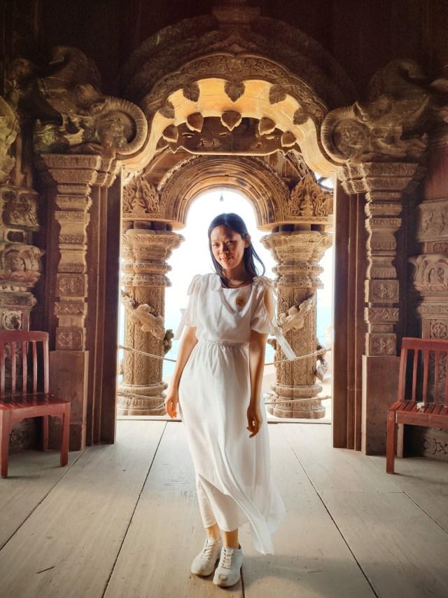 ภาพของผู้หญิงใส่ชุดกระโปรงสีขาว รองเท้าผ้าใบ ยืนอยู่หน้าประตูทางเข้าด้านหนึ่งของปราสาทสัจธรรม