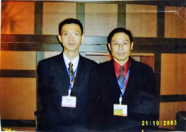 ภาพของผู้ชายใส่แว่นสองคนในชุดสูทสีเข้ม ห้อยป้ายชื่ออยู่ทั้งคู่