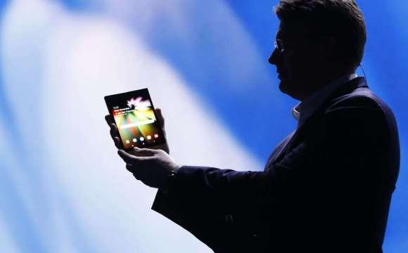 เงาของผู้ชายใส่สูทกำลังโชว์ Samsung Galaxy Fold อยู่