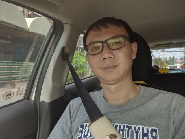ภาพของผู้ชายใส่แว่น เสื้อยืดสีเทา นั่งอยู่ในรถและคาดเข็มขัดนิรภัย