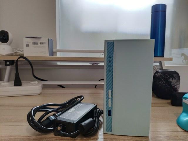 ตัวเครื่อง  QNAP TS-230 พร้อมอะแดปเตอร์ไฟ วางอยู่บนโต๊ะคอมพิวเตอร์ ด้านหลังทางขวามีลำโพงไร้สาย และกระบอกน้ำสีน้ำเงินวางอยู่ ส่วนด้านซ้ายมีกล้องวงจรปิด กล่อง และรางไฟ