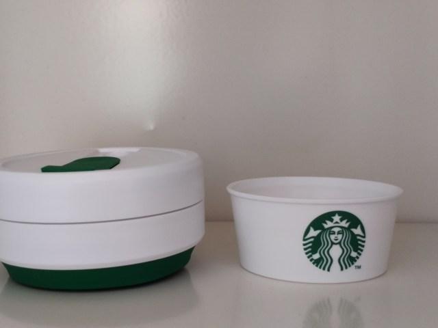 แก้ว Starbucks x Stojo ที่ย่อให้ยุบลงมาแล้ว โดยมีพลาสติกตัวจับแก้วสีขาว มีโลโก้ Starbucks วางอยู่ด้านขวา
