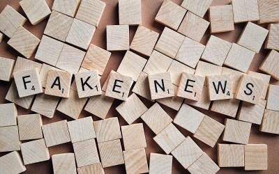 แป้นไม้สี่เหลี่ยมจำนวนมากวางเรียงรายอยู่บนโต๊ะ ด้านบนสุดมีแป้นไม้ที่มีตัวอักษรเรียงเป็นคำว่า FAKE NEWS