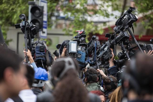 ภาพสื่อมวลชนกำลังรุมถ่ายภาพอะไรบางอย่าง มีกล้องถ่ายวิดีโอจำนวนมาก