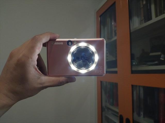 มือกำลังถือกล้อง CANON iNSPiC S หันเข้าหาตัวในโหมดถ่ายภาพเซลฟี่ ไฟ LED รอบๆ เลนส์