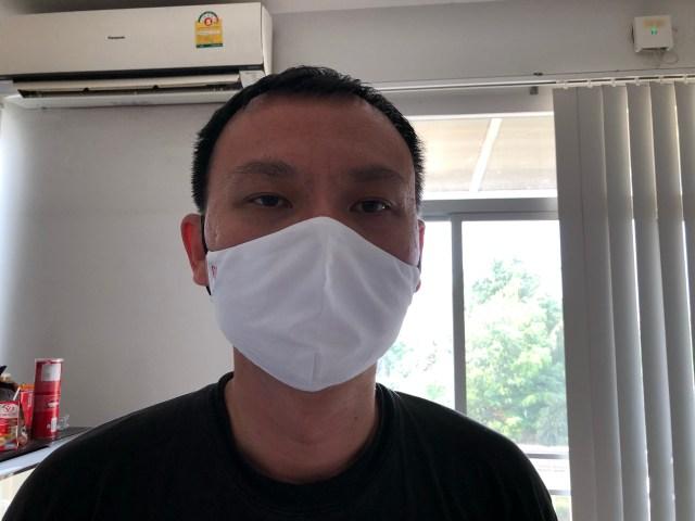 ภาพของผู้ชายใส่เสื้อสีดำ และสวมหน้ากากผ้า GQ White สีขาว