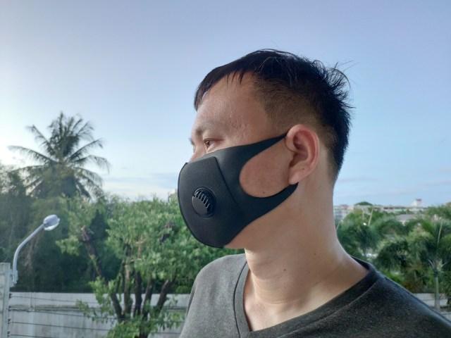 ผู้ชายผมสั้น ใส่เสื้อยืดคอวีสีเทาดำ ยืนหันข้าง ใส่หน้ากากโฟมวาล์ว Kireo สีดำ เห็นด้านที่เป็นวาล์วชัดเจน