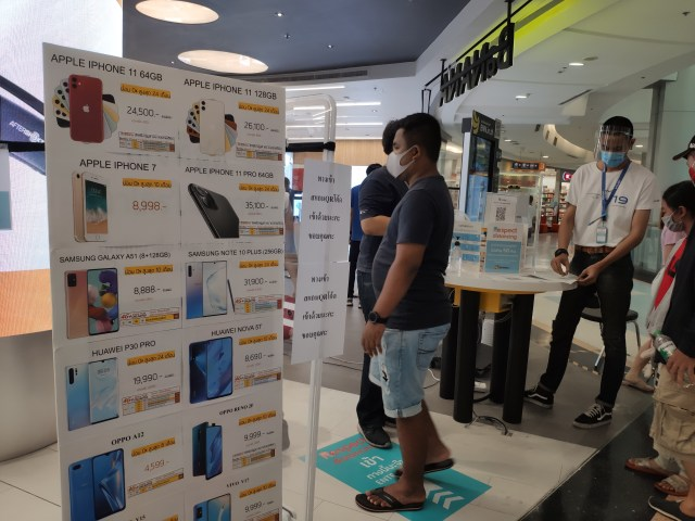 ผู้คนกำลังเดินเข้าร้าน Banana IT มีการจำกัดการเข้าของลูกค้า และต้องสแกน QR code เพื่อเช็กอินการเข้า