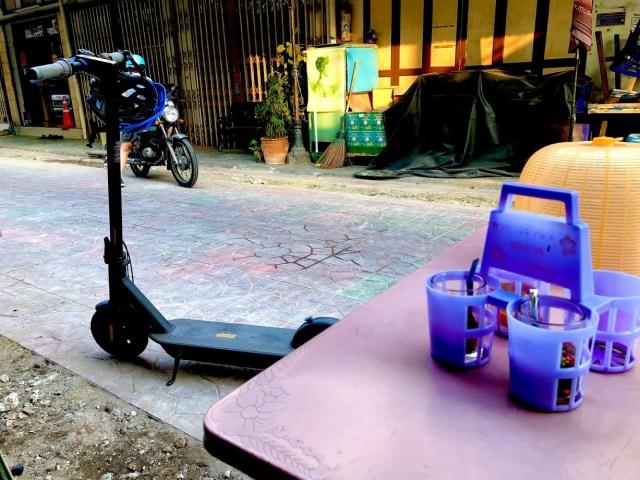 สกู๊ตเตอร์ไฟฟ้า Ninebot Kickscooter MAX กำลังจอดอยู่ริมถนน ใกล้ๆ กับโต๊ะของร้านอาหารข้างทาง ที่มีฝาชีสีเหลือง และพวงเครื่องปรุงวางอยู่บนโต๊ะ มีหมวกกันน็อกจักรยานสีฟ้าแขวนอยู่กับแฮนด์ของสกู๊ตเตอร์ไฟฟ้า