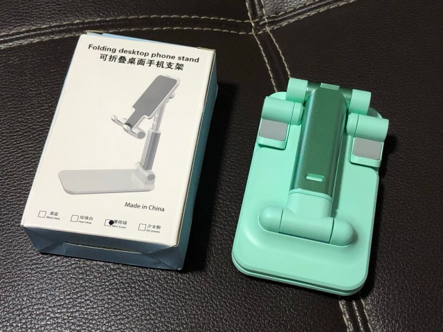 ขาตั้งสมาร์ทโฟนและแท็บเล็ตแบบพับได้ของ Choetech สีเขียวอ่อน กำลังพับอยู่ และมีกล่องใส่วางอยู่ข้างๆ