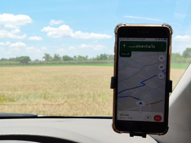 iPhone 8 Plus ที่วางอยู่บนตัวจับสมาร์ทโฟนติดรถ กำลังเปิด Google Maps อยู่ โดยมีแบ็กกราวด์เป็นทุ่งนาในจังหวัดนครปฐม