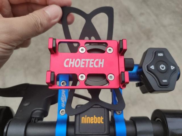 มือกำลังจับยางรัดสมาร์ทโฟน ที่ติดตั้งอยู่ด้านหลังของ Choetech smartphone holder