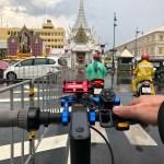 ภาพจากระนาบเดียวกับแฮนด์ของสกู๊ตเตอร์ไฟฟ้า Ninebot Kickscooter MAX ที่กำลังจอดรอไฟแดงอยู่บนถนน ด้านหน้าเป็นศาลเจ้าพ่อหลักเมือง