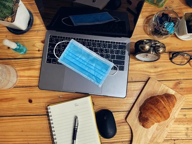 เครื่อง MacBook กำลังวางอยู่บนโต๊ะไม้ มีสมุดโน้ต เมาส์ และของต่างๆ วางอยู่ด้วย บนเครื่อง MacBook มีหน้ากากอนามัยวางอยู่