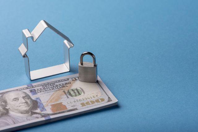 โครงเหล็กรูปบ้าน มีธนบัตรใบละ 100 ดอลล่าห์ปึกเล็กๆ วางอยู่โดยมีแม่กุญแจวางทับ