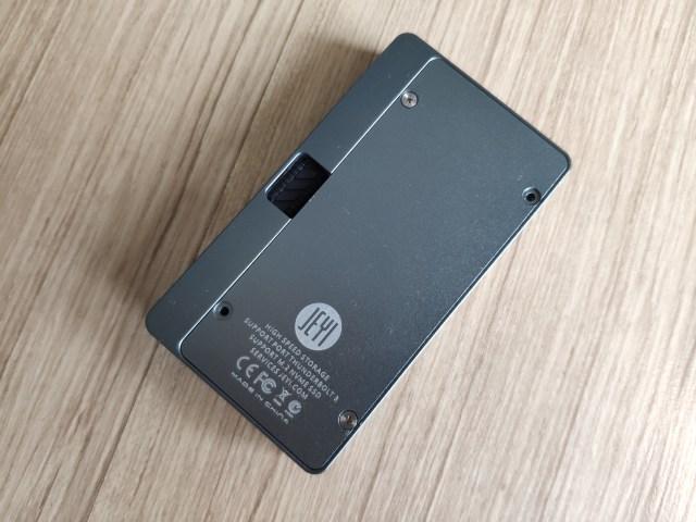 ด้านล่างของตัวกล่อง มีเจาะช่องเอาไว้สำหรับดันเอาสาย Thunderbolt 3 ออกมา และมีฝาปิดช่องใส่ SSD