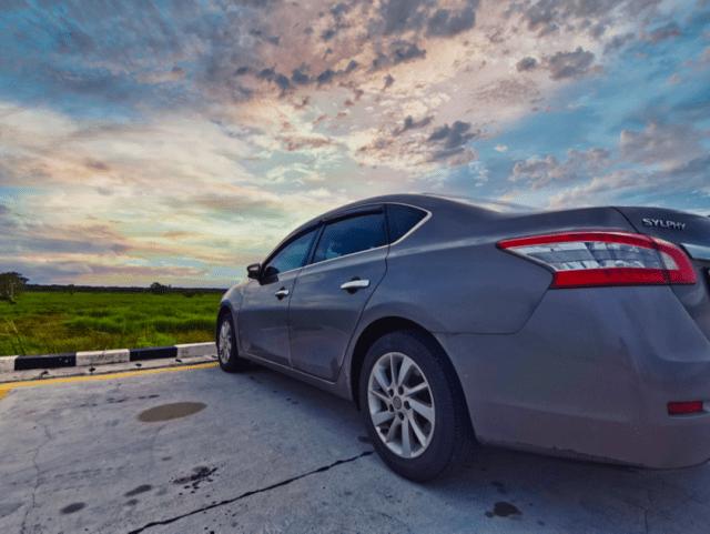 ภาพของรถยนต์ Nissan Sylphy กำลังจอดอยู่ โดยมีเบื้องหน้าเป็นทุ่งหญ้าและท้องฟ้า เป็นภาพหลังปรับแต่งด้วยโปรแกรม Luminar 4 แล้ว ท้องฟ้าเป็นแบบพระอาทิตย์ตกดิน