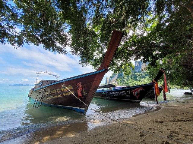 หาดทราย และวิวทะเล โดยมีเรือหางยาวจอดอยู่สามลำ