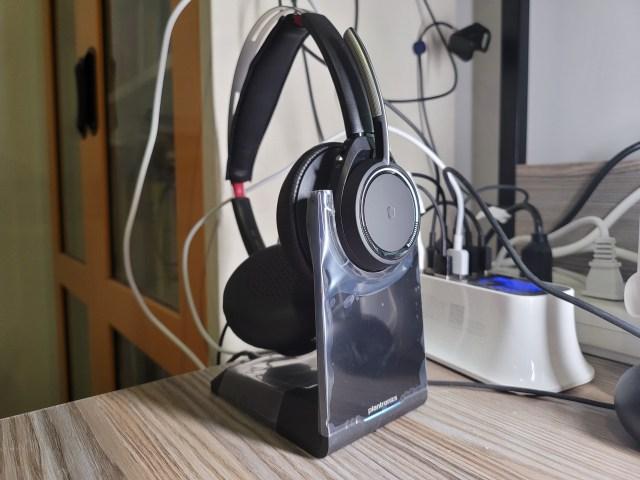 หูฟัง Plantronics Voyager Focus UC กำลังชาร์จแบตเตอรี่อยู่บนแท่นชาร์จ