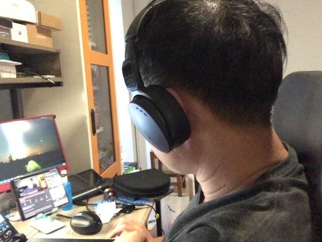 ผู้ชายผมสั้น กำลังสวมหูฟัง EPOS Sennheiser ADAPT 560 ดู YouTube จากสมาร์ทโฟนอยู่