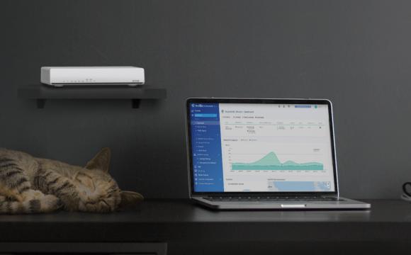 QHora-301W วางอยู่บนชั้นวางเล็กๆ ติดกำแพง โดยมีแมวนอนอยู่ด้านล่าง ข้างๆ เครื่อง MacBook Pro และแก้วกาแฟ