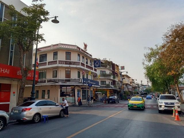 ภาพของถนนและอาคาร มีรถยนต์จอดอยู่สองข้างทาง และมีรถแท็กซี่กำลังวิ่งเข้ามา