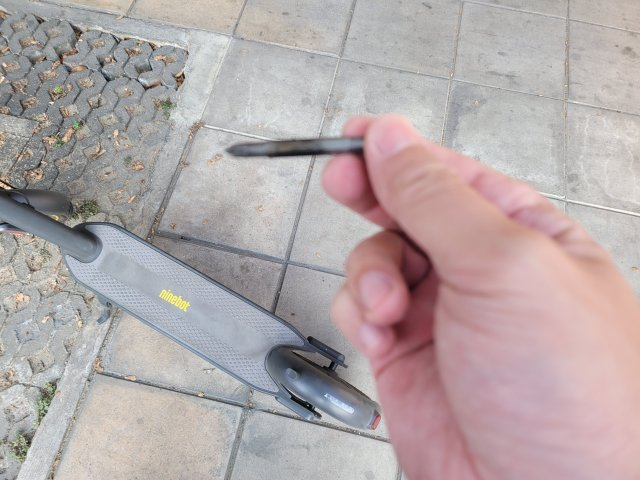 ภาพระยะใกล้ของมือที่หยิบปลายไขควงแบบเปลี่ยนหัวได้ โดยมีสกู๊ตเตอร์ไฟฟ้า Ninebot Kickscooter MAX อยู่