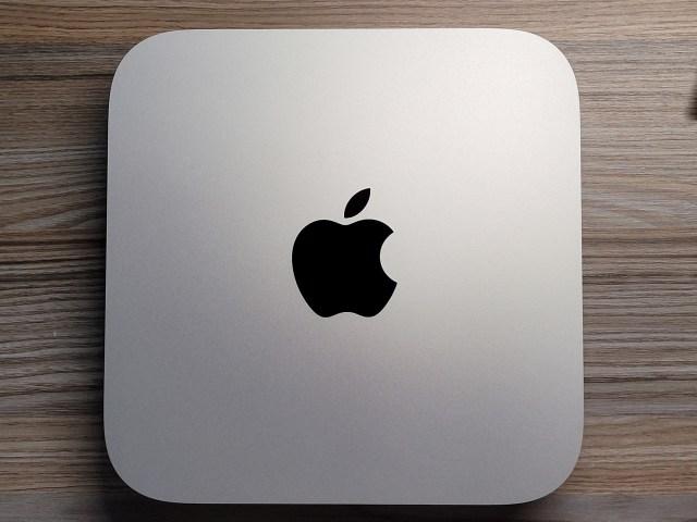 ภาพด้านบนของเครื่อง Mac mini รุ่นใช้ชิป Apple M1 ตัวเครื่องเป้นสีเงิน มีโลโก้ Apple สีดำ เป็นมันวาว อยู่ตรงกลาง