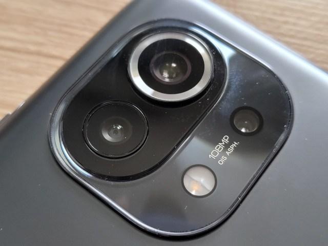 ภาพระยะใกล้ของกล้อง Xiaomi Mi 11 5G แสดงให้เห็นถึงเลนส์กล้องสามเลนส์ และข้อความ 108MP OIS ASPH