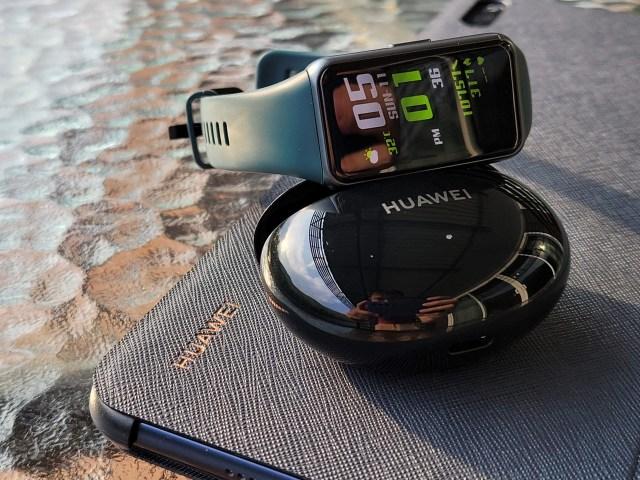 สมาร์ทแบนด์ Huawei Band 6 วางอยู่กับตลับหูฟัง Huawei FreeBud 3i และแท็บเล็ต Huawei