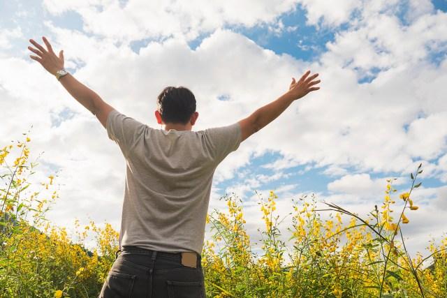 ผู้ชายอยู่ในทุ่งกว้าง กำลังยืนผายมือออกสองข้างอย่างสบายใจในอิสระที่อยู่ท่ามกลางธรรมชาติ
