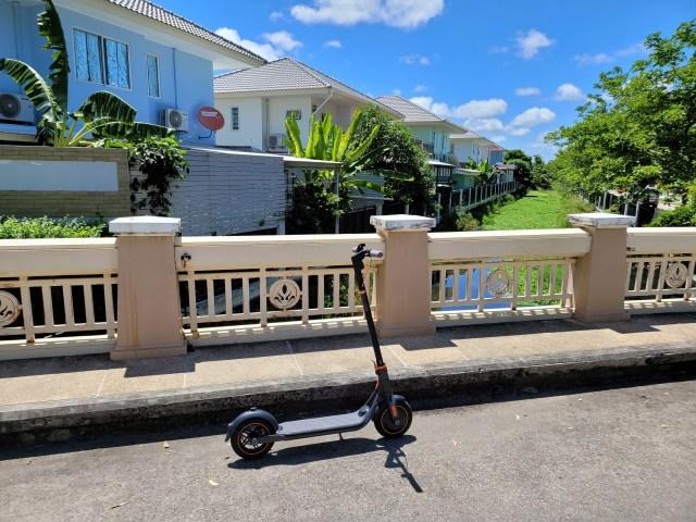 สกู๊ตเตอร์ไฟฟ้า Ninebot Kickscooter F40 จอดอยู่ริมถนนบนสะพานข้ามคลองในหมู่บ้านจัดสรร