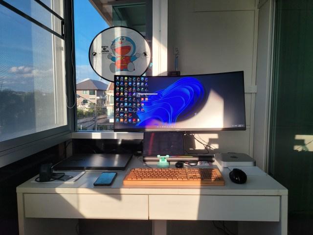 โต๊ะทำงาน มีคอมพิวเตอร์ จอคอมพิวเตอร์ คีย์บอร์ด เมาส์ แท็บเล็ต โดนแสงแดดยามเย็นส่อง