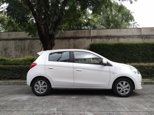รูปของรถยนต์มิตซูบิชิ มิราจ สีขาว จอดอยู่ริมถนน