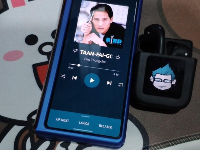 สมาร์ทโฟน Samsung Galaxy Z Fold 2 กำลังเปิดเพลงพี่เบิร์ด ธงไชย วางอยู่ข้างหูฟัง Amorus NR-550 TWS