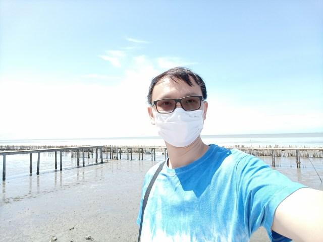 ผู้ชายผมสั้น ใส่แว่น สวมหน้ากากอนามัย เสื้อยืดคอกลมสีฟ้า ถ่ายเซลฟี่อยู่บริเวณพื้นที่ชายเลนใกล้กับทะเล ภาพมีลักษณะ Overexposed เล็กน้อย เพราะโหมด HDR ของกล้องไม่ทำงาน