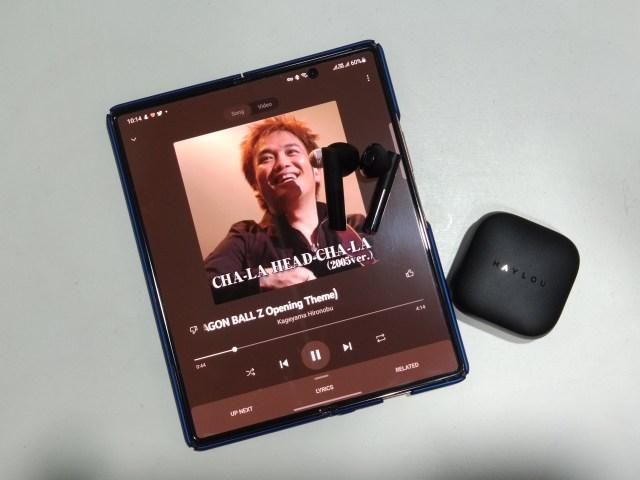 Samsung Galaxy Z Fold 2 กำลังฟังเพลง โดยมีหูฟัง HAYLOU GT6 วางอยู่บนหน้าจอ และมีกล่องใส่วางอยู่ข้างๆ
