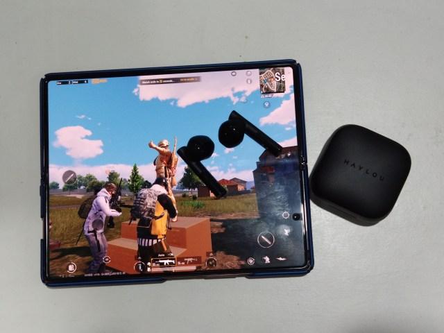 Samsung Galaxy Z Fold 2 กำลังเล่นเกม PUBG โดยมีหูฟัง HAYLOU GT6 วางอยู่บนหน้าจอ และมีกล่องใส่วางอยู่ข้างๆ