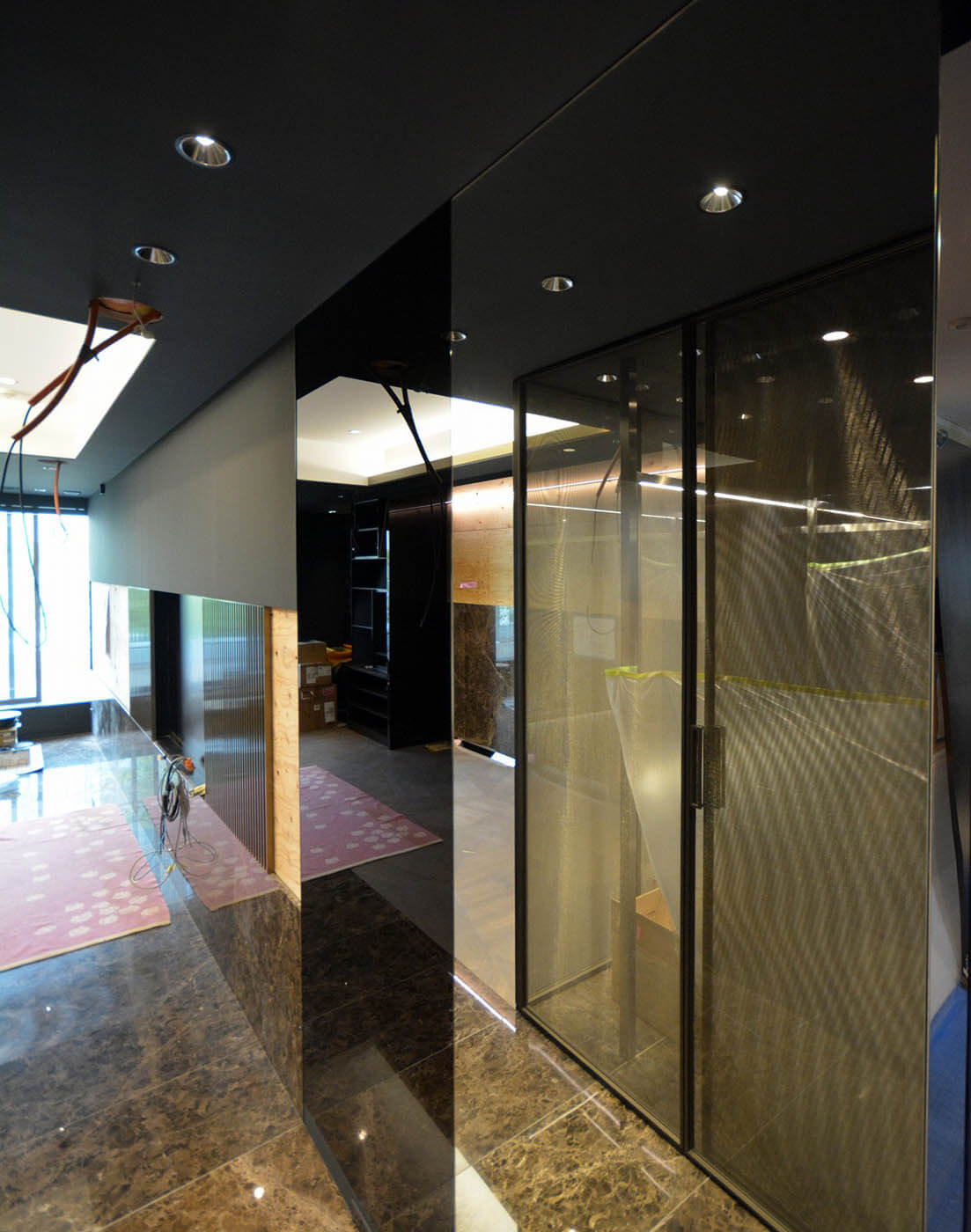 ミラーとカラーガラスと大理石の腰壁とテレビを組み込んだ主寝室の壁デザイン