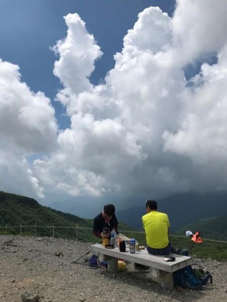夏の入道雲をバックに昼食をとる登山者