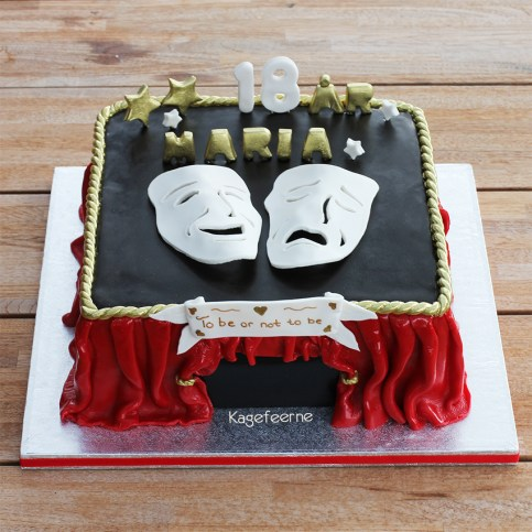 Teater kage med tæppet trukket fra og teatermasker og Marias navn i guld på toppen.