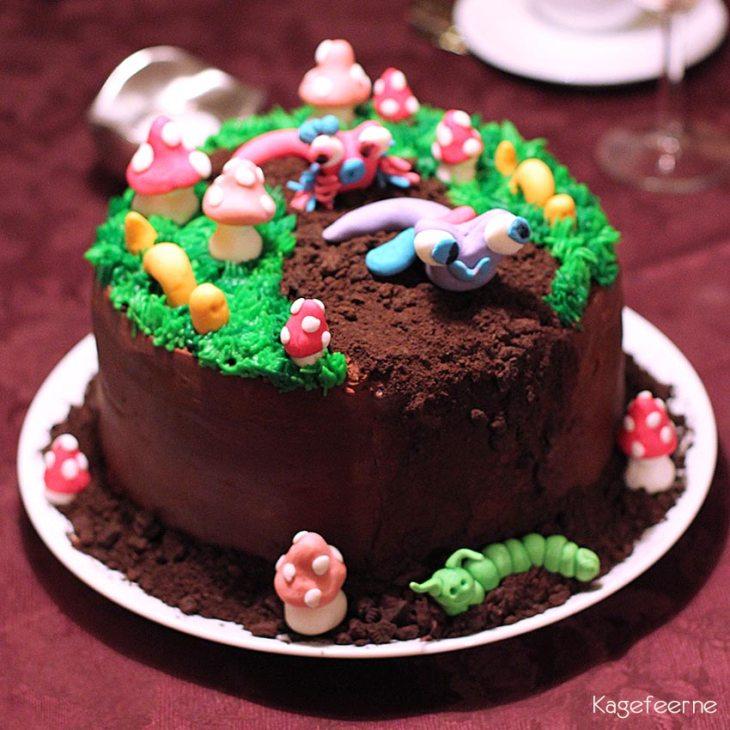 Kage der ligner en jordbund med fondant snegle, orme og paddehatte