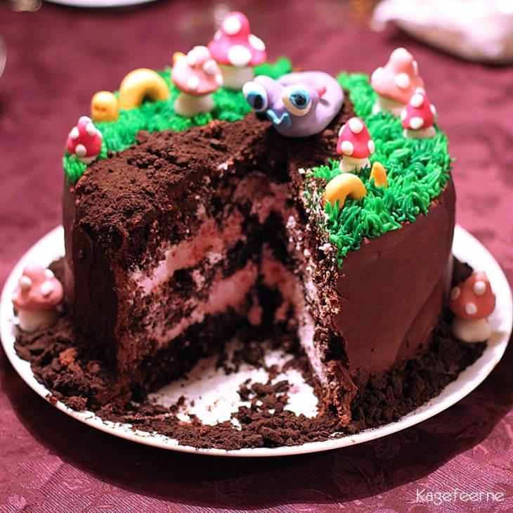 Kage der ligner en jordbund med fondant snegle, orme og paddehatte, hvor der er taget et par stykker