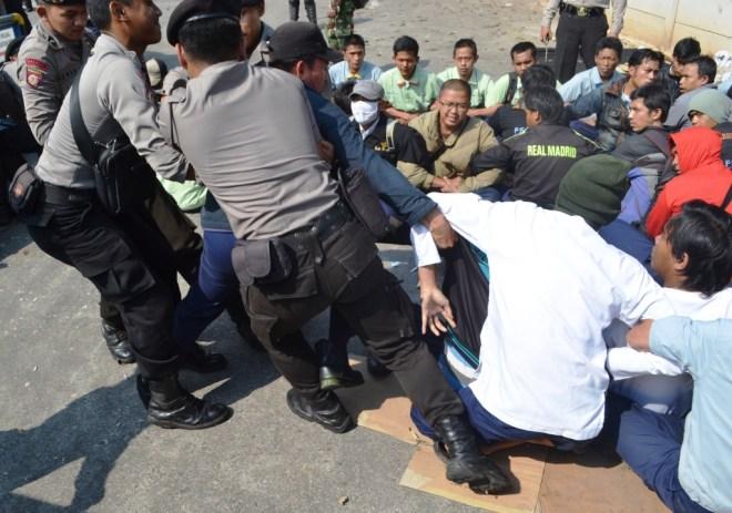 Aparat mengangkat paksa buruh untuk keluar dari pintu gerbang | Foto: Tim Media FSPMI Purwakarta