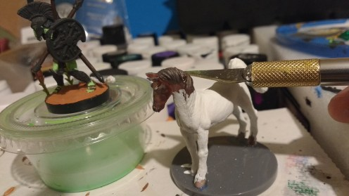 An inexpensive toy horse with an exacto knife poised to cut off it's head.
