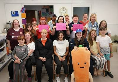 """A group of women and children stand together smiling, holding up signs that say """"thank you, we raised £1005"""". There is a giant carrot teddy bear at the front."""