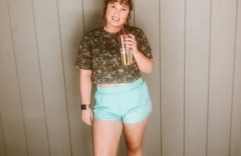 Kaitey standing in fitness clothes with a water tumbler